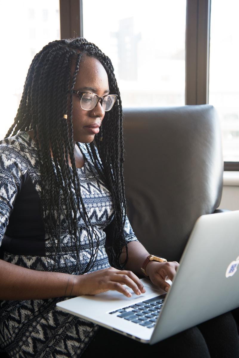 shallow focus photo of woman using MacBook